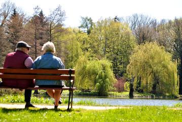 Fototapeta Zdjęcie przedstawiające parę starszych ludzi siedzącą na ławce w parku obraz