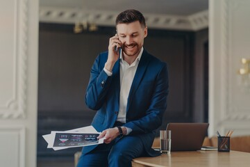 Fototapeta Happy handsome businessman talking on phone while sitting on table at luxury apartment obraz