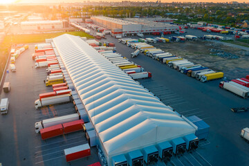 Logistics park with warehouse and loading hub. Semi-trailers trucks stand at ramps and wait for load and unload goods. Aerial view at sunset - fototapety na wymiar