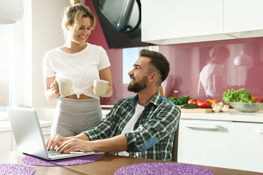 Happy couple using laptop in the kitchen at morning
