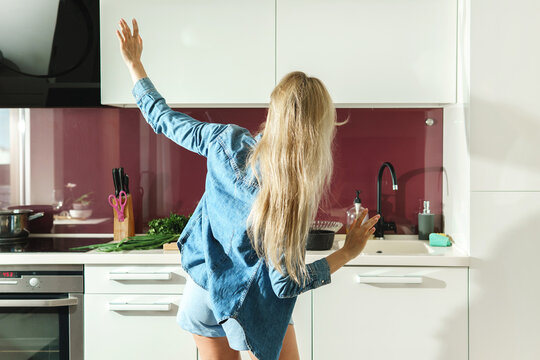Attractive woman dancing on the kitchen while cooking during sunny morning