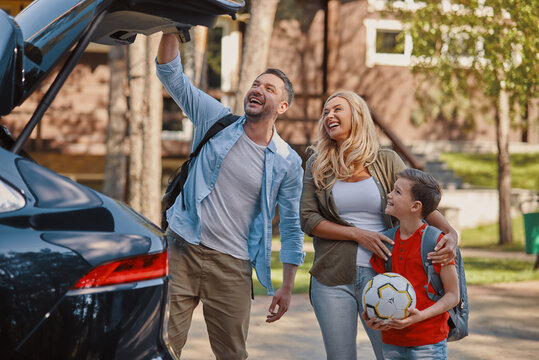 Happy family with little boy packing stuff into the car while standing in front of the house tpgether