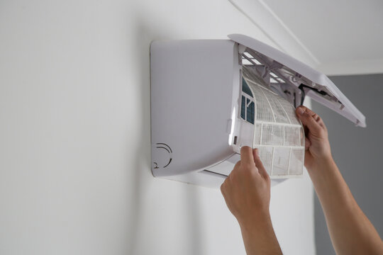 Man putting new clean air filter on air conditioner.