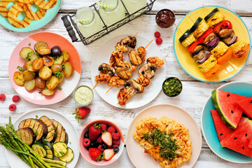 Vegan summer bbq or picnic table scene. Overhead view on a white wood background. Fruit, grilled vegetables, skewers, cauliflower steak and lemonade. Meat substitute concept.