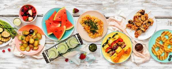 Wall Murals London Vegan summer bbq or picnic table scene.Above view on a white wood banner background. Fruit, grilled vegetables, skewers, cauliflower steak and lemonade. Meat substitute concept.