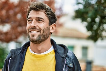 Handsome hispanic man with beard smiling happy outdoors