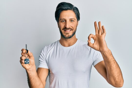 Young hispanic man holding keys of new home doing ok sign with fingers, smiling friendly gesturing excellent symbol