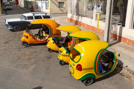 Multiple cocotaxi in Havana, Cuba. Moto taxi yellow vehicle visible all around La Habana downtown. Popular option of transportation for tourists.