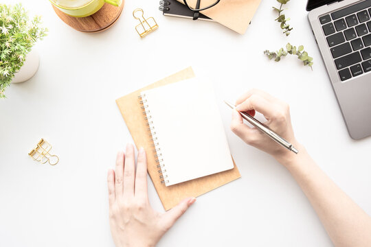 Business woman is going to write something on blank notebook over white office desk table, top view.