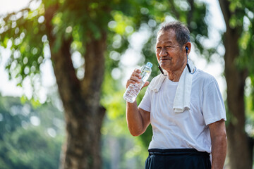 Happy thirsty senior man drinking fresh water after sports in park, Concept of senior healthy lifestyle.