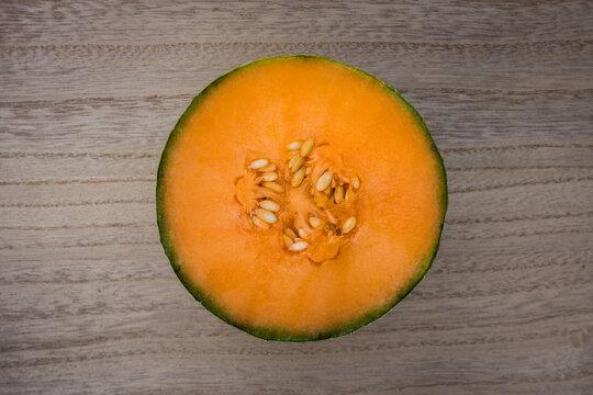 Melon coupé sur table en bois, vue de dessus.