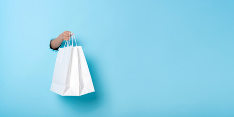 Woman hand holding paper shopping bag on blue banner background. Discounts and sale concept. Panoramic image - fototapety na wymiar