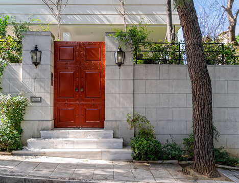 wealthy family house front entrance red door by the sidewalk, Athens Greece