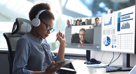 African american entrepreneur using in headphones talking to her colleagues in video conference....