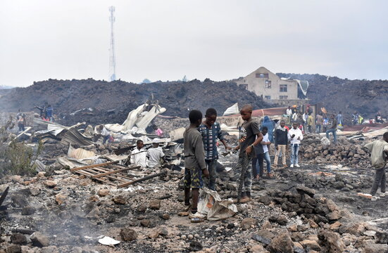 Residents pick up remains of their destroyed homes from the smouldering lava deposited by the eruption of Mount Nyiragongo volcano near Goma