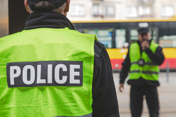 Word police written on reflective vests of police officers - fototapety na wymiar