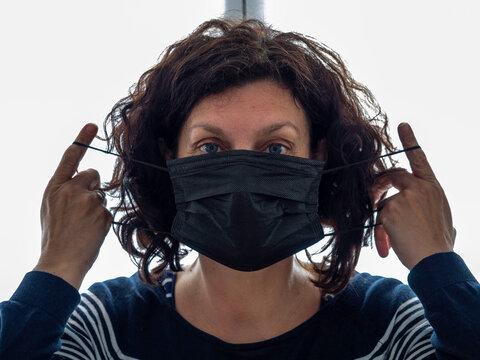 Femme qui met en place un masque noir pour éviter de contaminer les autres personnes des virus et du covid 19