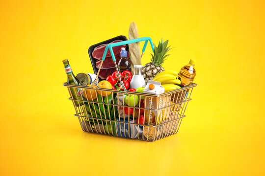 Shopping basket full of variety of grocery products, food and drink on yellow background.