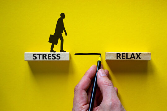Stress or relax symbol. Wooden blocks with words 'Stress, Relax'. Yellow background. Businessman hand, businessman icon. Psychological, business and stress or relax concept. Copy space.