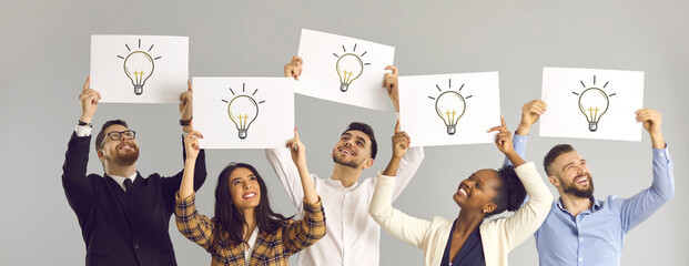 Fototapeta Sharing experiences and ideas. Interracial colleagues hold a white layout with light bulbs symbolizing a new idea. Group of people expressing their opinion holding posters on a gray background. obraz