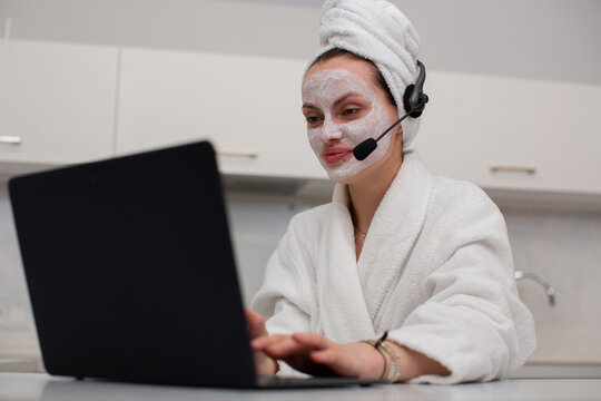 A girl in a home dressing gown works behind a laptop in a headset, sitting at home in the kitchen. The concept of remote work. High quality photo