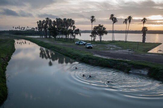 Migrants from Central America swim through an inlet of Walker Lake as being chased by U.S. Border Patrol