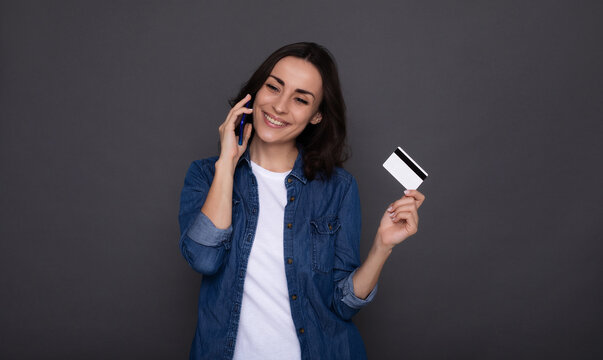 Young successful happy woman with a credit card in hand during online shopping