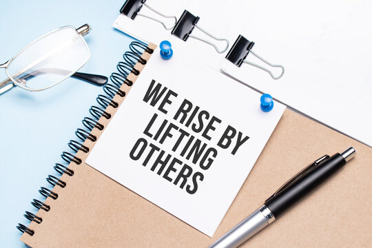 Notepad with We Rise by Lifting Others text on the office table with glasses, notepad and paper with clips.