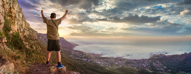 Victory and success after a hike up Table Mountain at sunset with dramatic sun rays. Great outdoors adventure and travel holiday destination, Cape Town, South Africa Wall mural