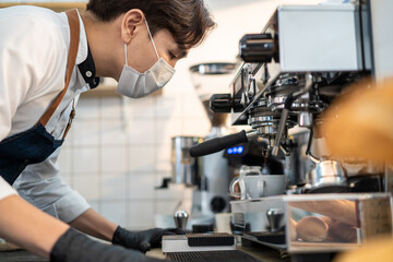 Asian male barista wearing face mask operating coffee machine in cafe.