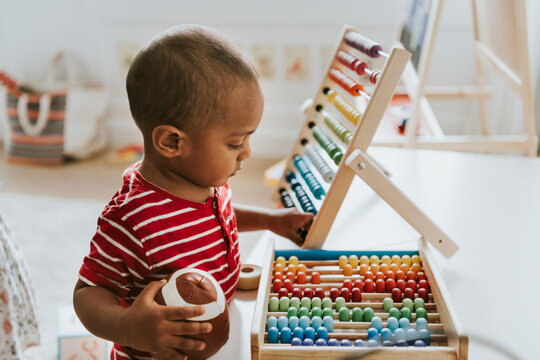 Kid playing with a colorful wooden abacus