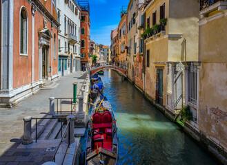 Narrow canal with gondola in Venice, Italy. Architecture and landmark of Venice. Cozy cityscape of Venice.