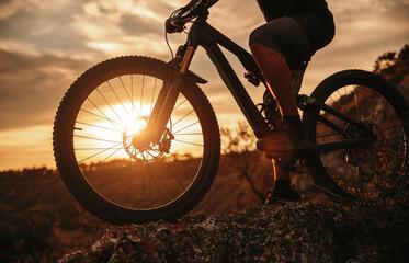 Obraz Crop man riding bicycle at sunset - fototapety do salonu