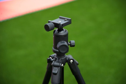 Close up photo of tripod with ball head for camera on stadium