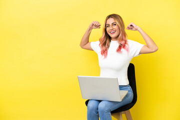 Young woman sitting on a chair with laptop over isolated yellow background doing strong gesture - fototapety na wymiar