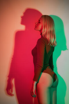 Stylish model stands with her eyes closed in neon light, her back turned. Young blond woman in bodysuit.