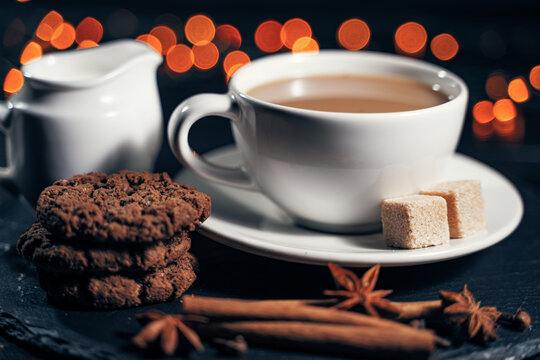 A cup of warming coffee with chocolate chip cookies and aromatic cinnamon.