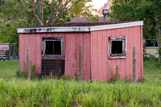 Old pink and salmon painted wooden hut type storage shed used for lawn maintenance tools and farm equipment with open windows and shingle roof found in a residential backyard with overgrown grass.