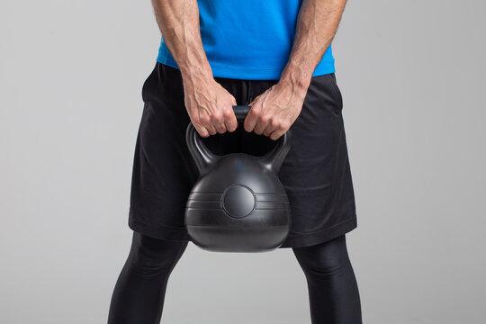 Man holding kettlebell on gray background