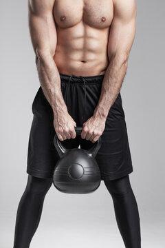 Strong muscular man holding kettlebell