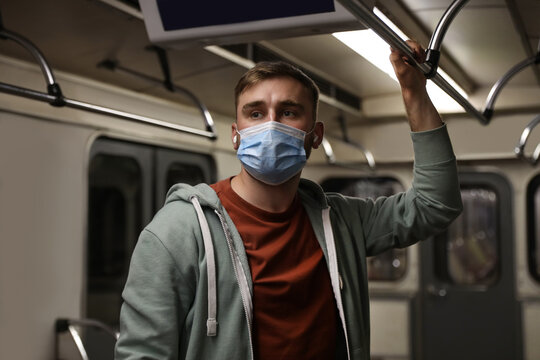 Young man in protective mask with earphones travelling by subway train. Public transport