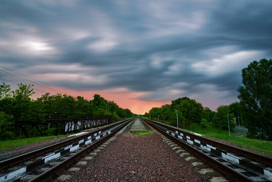 Scenic view of railways going straight ahead to sunset with moving clouds