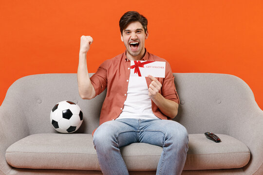 Young man football fan in shirt support team with soccer ball sit sofa home watch tv live stream hold gift voucher flyer mock up do winner gesture isolated on orange background People sport concept.