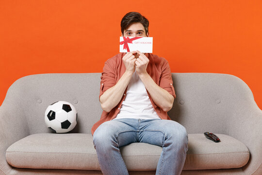 Young man football fan in shirt support team with soccer ball sit sofa home watch tv live stream cover mouth hiding with gift voucher flyer mock up isolated on orange background People sport concept