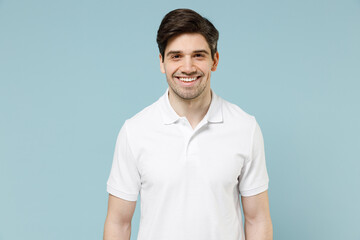 Young fun smiling happy attractive unshaven cheerful caucasian man 20s in white casual basic t-shirt looking camera isolated on pastel blue color background studio portrait. People lifestyle concept