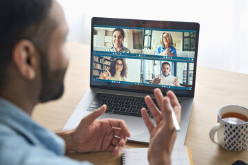 Latin indian businessman having virtual team meeting group call chatting with diverse people in...