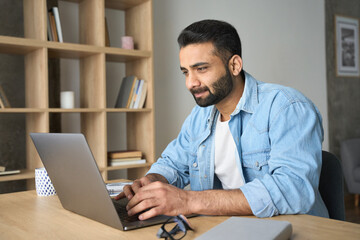 Fototapeta Young Indian Hispanic businessman using computer working remotely from modern home office. Latin student having virtual training on laptop typing watching distant online webinar during quarantine. obraz