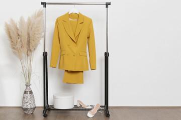 Fototapeta Women's Clothes. Clothes rack, yellow blazer and trousers in fashion atelier. obraz
