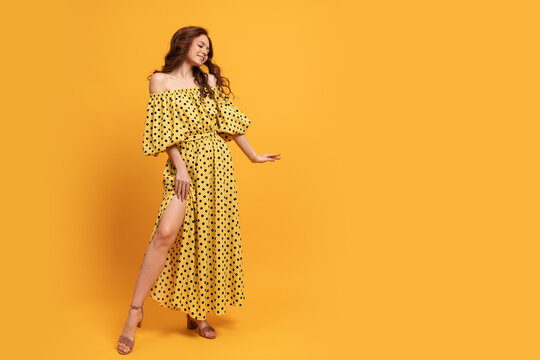 Red-head woman in yellow dress posing in studio. Summer mood. Full lenght.
