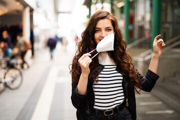 Obraz Junge Frau zieht freudig ihre FFP2 Maske aus, Ende der Maskenpflicht  - fototapety do salonu